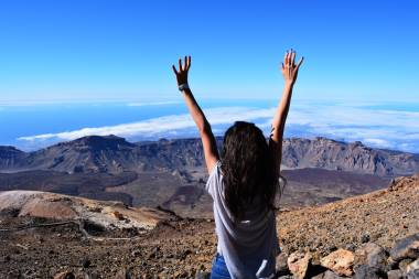 woman-standing-on-mountain-while-raising-her-hands-1053451
